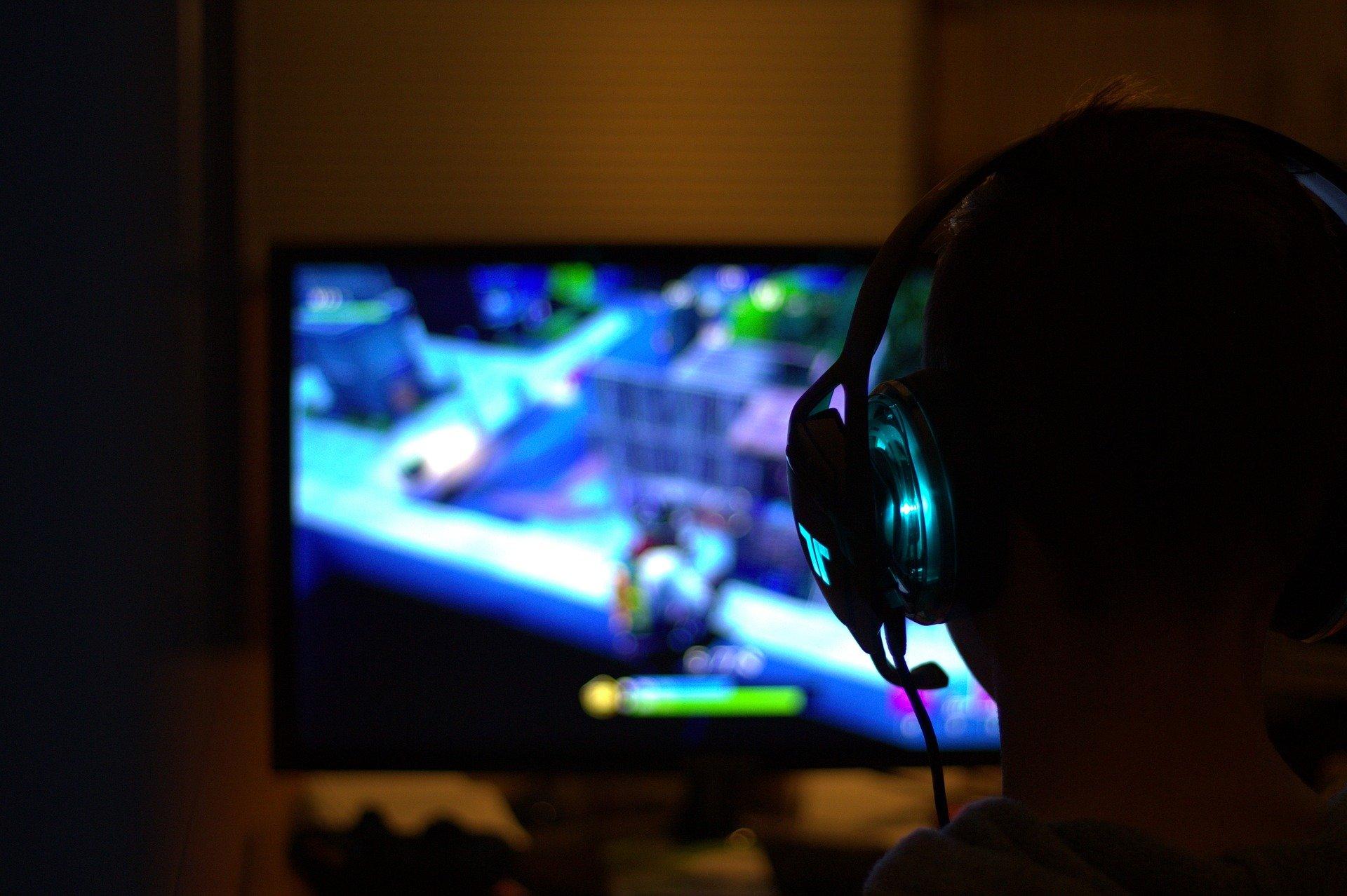 mężczyzna grający na komputerze w grę komputerową; ma na sobie słuchawki, na ekranie widać rozgrywkę