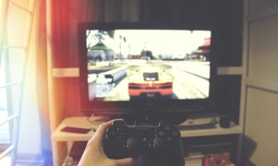 ktoś gra na konsoli; widok z oczu; w ręku trzyma kontroler; na ekranie rozgrywa się gra