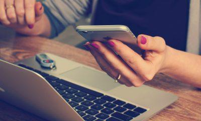 laptop uzyskany poprzez wynajem laptopów, który leży na stole, przy którym siedzi kobieta, która trzyma w ręku telefon