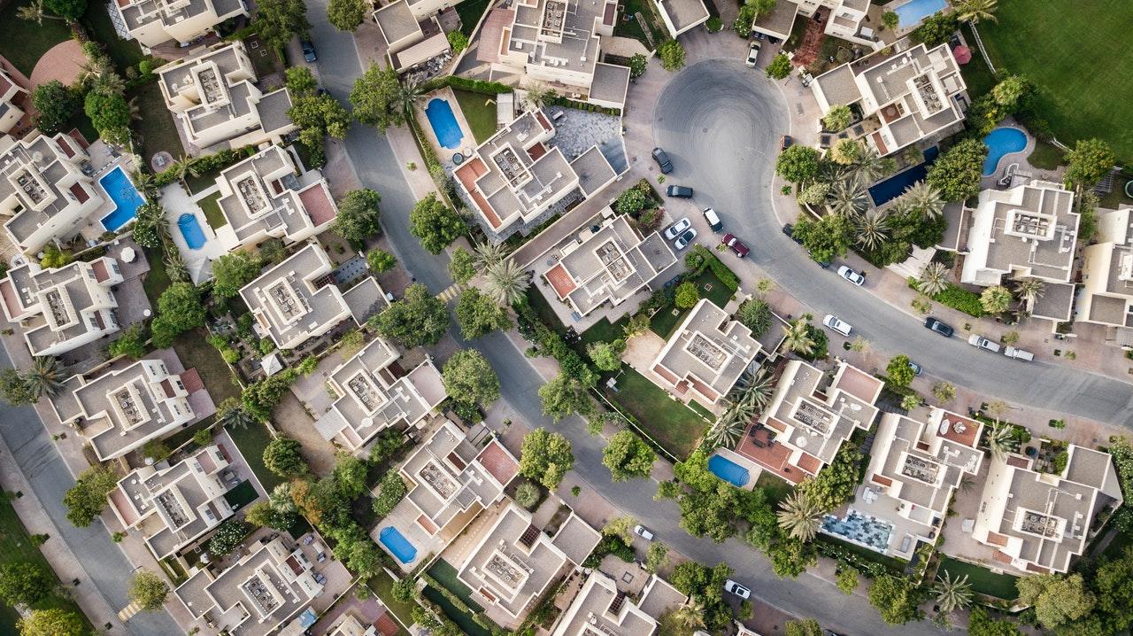 Nieruchomości z problemami z gdańskiego skupu nieruchomości z problemami. Widać bogatą dzielnicę z lotu ptaka. Baseny, samochody itd.